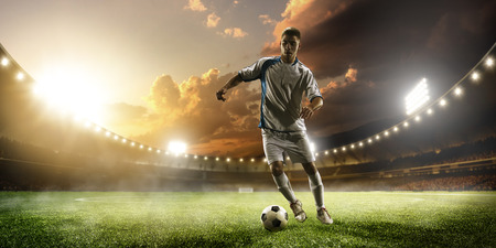 Photo pour Soccer player in action on sunset stadium background - image libre de droit