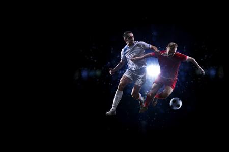 Photo pour Soccer players in action over black background - image libre de droit