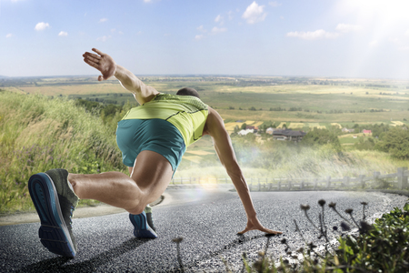 Photo for Running athlete man. Male runner sprinting during outdoors training for marathon run. Athletic fit young sport fitness model in his twenties in full body length on road outside in nature. - Royalty Free Image