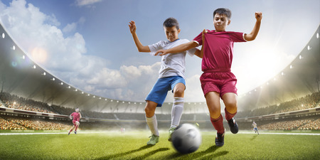 Photo for Childrens are playing soccer on grand arena in sunlights - Royalty Free Image