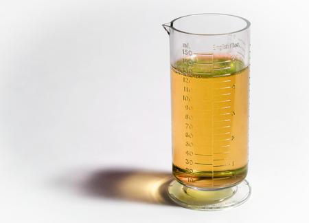 Foto de Beaker or flask with yellow liquid isolated on white background - Imagen libre de derechos
