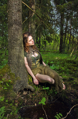 Photo for forest nymph sits leaning against the old tree - Royalty Free Image