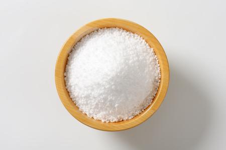 Photo pour Coarse grained salt in wooden bowl - image libre de droit