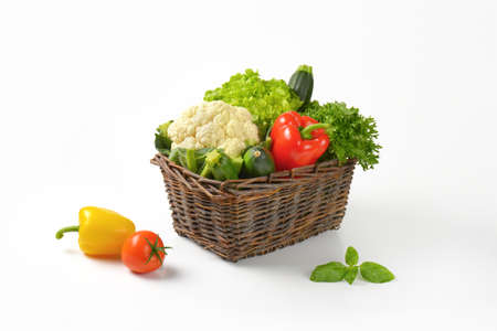 basket of fresh vegetables on white background