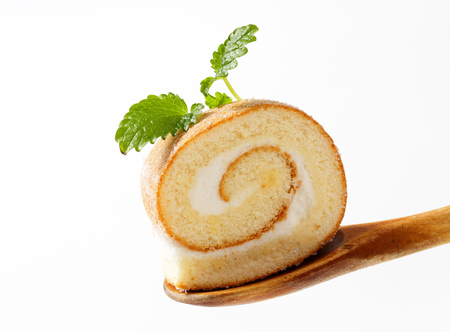 Photo for Slice of sweet creamy roll on a wooden spoon - Royalty Free Image