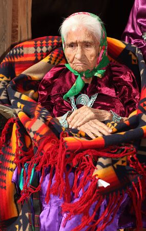 Navajo Woman Deep in Thought With Hands Crossed in Bright Traditional Clothing