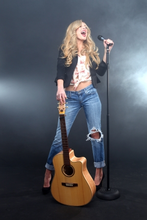 Photo for Beautiful Woman Singing on Stage With Mic and Guitar - Royalty Free Image