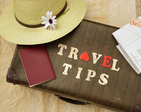 Foto de Summer travel hat,flower,old suitcase,brown passport,map and wooden letters: travel tips - Imagen libre de derechos