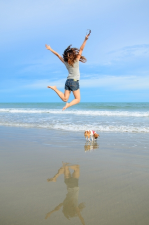 Foto de Young woman jumping with her cute jack russel puppy on the beach, Thailand - Imagen libre de derechos