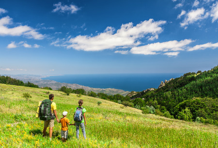 Foto de Happy family walking with backpacks on field and looking at the sea - Imagen libre de derechos