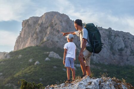 Photo pour Father with backpack shows his little son to big mountain - image libre de droit