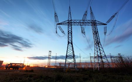 Foto de electricity transmission pylon silhouetted against blue sky at dusk - Imagen libre de derechos