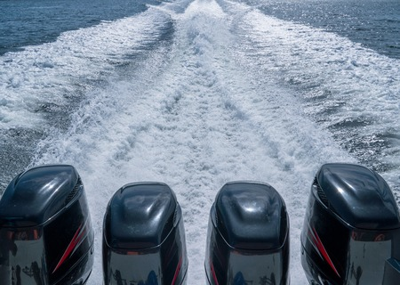 Foto de Four Boat motors left a pass of foam on the water - Imagen libre de derechos