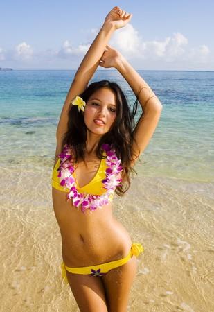beautiful Polynesian woman in a yellow bikini smiling at a Hawaii beach