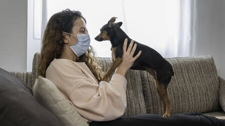 Foto de Coronavirus. Young woman playing with her dog in isolation at home, protected from the virus. Pandemic. Social distance - Imagen libre de derechos