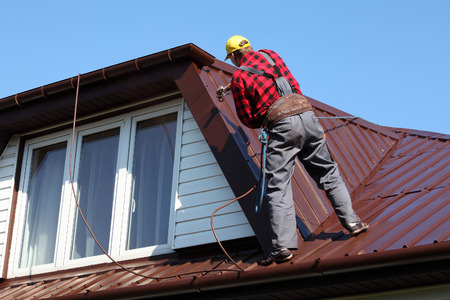 Photo pour roofer builder worker with pulverizer spraying paint on metal sheet roof - image libre de droit