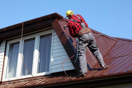 Foto de roofer builder worker with pulverizer spraying paint on metal sheet roof - Imagen libre de derechos