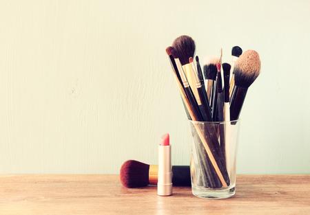 Photo pour make up brushes over wooden table - image libre de droit