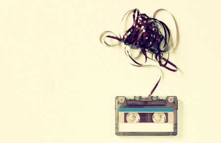 Photo for Cassette tape over wooden table with tangled ribbon. top view. retro filter - Royalty Free Image