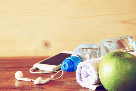 Foto per low key  image of fitness concept with bottle of water, mobile phone with earphones, towel and apple over wooden background. filtered image with selective focus - Immagine Royalty Free