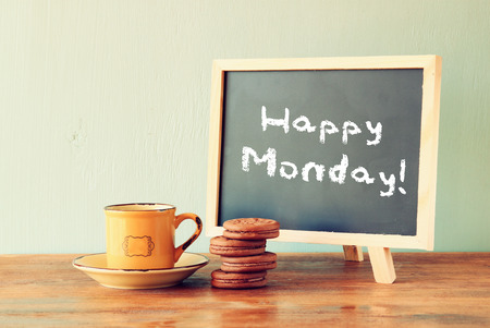 Foto de blackboard with the phrase happy monday next to cup of coffee and cookies - Imagen libre de derechos