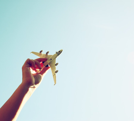 Foto de close up photo of woman hand holding toy airplane against blue sky with clouds - Imagen libre de derechos