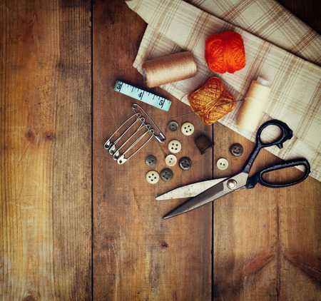 Foto per Vintage Background with sewing tools and sewing kit over wooden textured background - Immagine Royalty Free