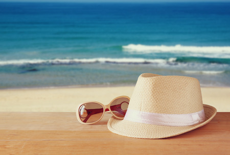 Foto de fedora hat and stack of books over wooden table and sea landscape background. relaxation or vacation concept - Imagen libre de derechos