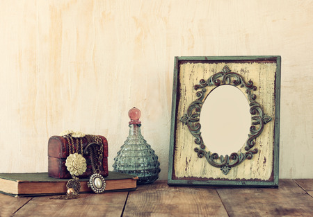 Photo pour image of victorian vintage antique classical frame jewelry and perfume bottles on wooden table. filtered image - image libre de droit