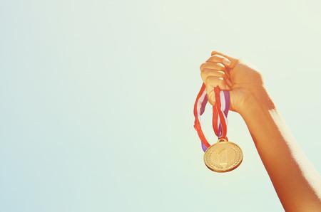 Foto de woman hand raised, holding gold medal against sky - Imagen libre de derechos