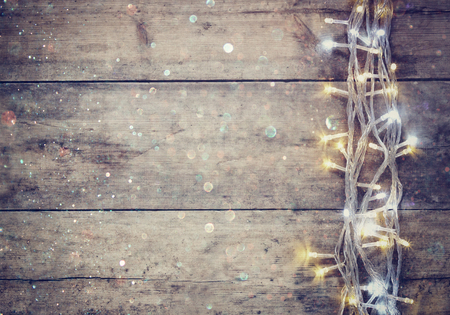 Photo pour Christmas warm gold garland lights on wooden rustic background. filtered image with glitter overlay - image libre de droit