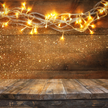 Foto de wood board table in front of Christmas warm gold garland lights on wooden rustic background. filtered image. selective focus. glitter overlay - Imagen libre de derechos