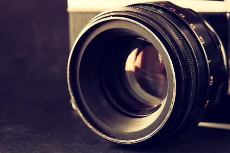 Foto de close up photo of old camera lens over wooden table. image is retro filtered. selective focus - Imagen libre de derechos