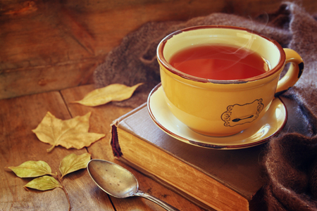 Photo for Cup of tea with old book, autumn leaves and a warm scarf on wooden table - Royalty Free Image