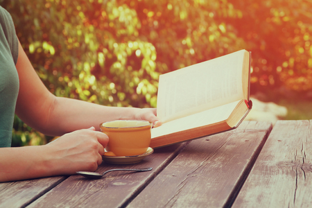Photo for close up image of woman reading book outdoors, next to wooden table and coffee cup at afternoon. filtered image. filtered image. selective focus - Royalty Free Image