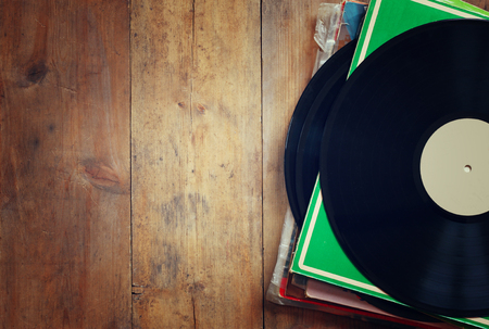 Photo pour records stack with record on top over wooden table. vintage filtered - image libre de droit