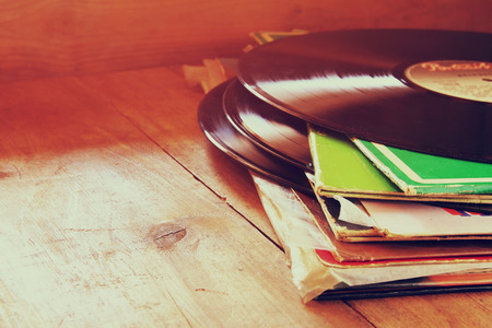 Photo pour selective focus of records stack with record on top over wooden table. vintage filtered - image libre de droit