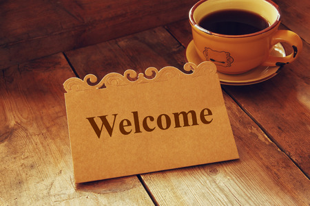 Foto per welcome card over wooden table next to coffee cup - Immagine Royalty Free