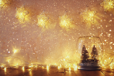 Foto de low key and vintage filtered image of christmas trees in mason jar with garland warm lights. selective focus - Imagen libre de derechos