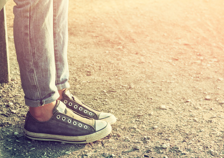 Photo for close up image of girl in sneakers sitting on the bench. - Royalty Free Image