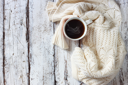Photo pour top view image of white cozy knitted sweater with to cup of coffee on a wooden table - image libre de droit