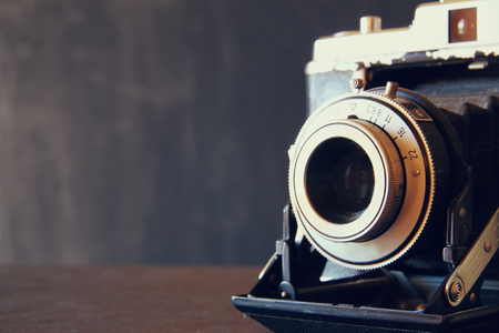 Photo for close up photo of old vintage camera lens over wooden table. selective focus - Royalty Free Image