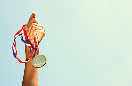 Photo pour woman hand raised, holding gold medal against sky. award and victory concept - image libre de droit