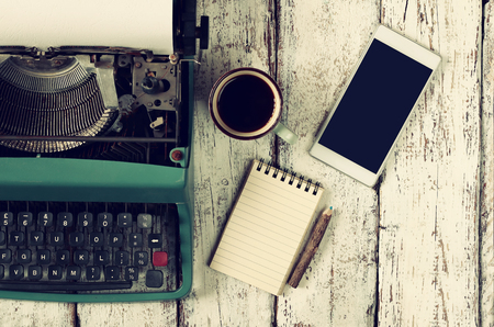 Foto de retro filtered image of vintage typewriter, blank notebook, cup of coffee and smartphone on wooden table - Imagen libre de derechos