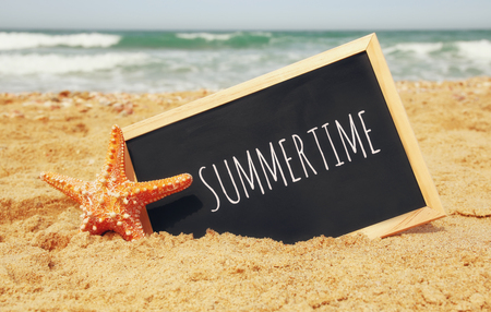 Foto de starfish and clachboard with phrase: SUMMERTIME, on sea sand and ocean horizon - Imagen libre de derechos