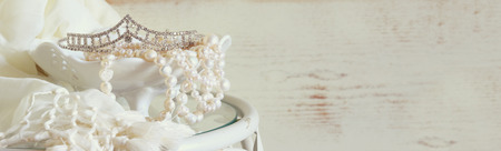 Foto de website banner background of white pearls necklace and diamond tiara on vintage table. toned image. selective focus - Imagen libre de derechos
