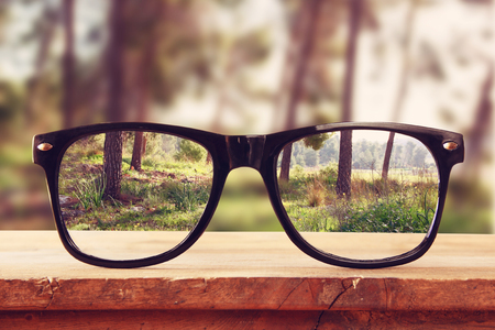 Foto de hipster glasses on a wooden rustic table in front of the forest. vintage filtered - Imagen libre de derechos