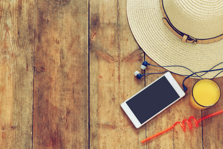 Photo for top view image of summer hat, fruit cocktail and cell phone on wooden deck - Royalty Free Image