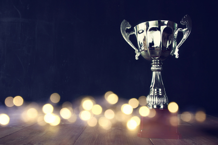 Photo pour low key image of trophy over wooden table and dark background, with abstract shiny lights - image libre de droit