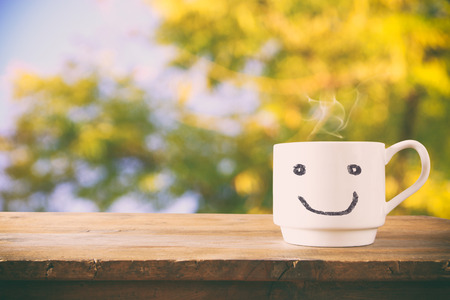 Photo for image of coffee cup with happy face over wooden table and tree leaves - Royalty Free Image